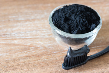 Close up view of black charcoal toothpaste and toothbrush ion wooden background