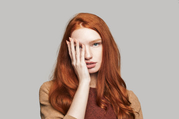 What is there Portrait of young and cute teenage girl with red silky hair covering face with hand and looking at camera while standing against grey background