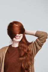 Natural beauty. Portrait of cheerful and young redhead woman playing with her hair and smiling while standing against grey background