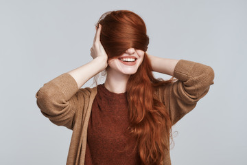 Playful mood. Portrait of cheerful and young redhead woman playing with her hair and smiling while standing against grey background