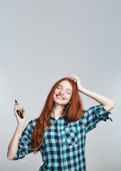 Carefree and happy. Portrait of cheerful and pretty young redhead lady in headphones listening music and smiling while standing against grey background
