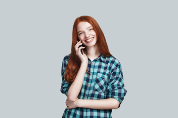 Good news Young and cute redhead woman in casual wear is talking on the phone and smiling while standing against grey background