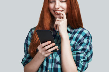 Surfing the net. Young and cute redhead woman in casual wear using her smart phone and smiling while standing against grey background