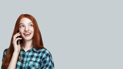 Glad to hear you Young and cute redhead woman in casual wear is talking on the phone and smiling while standing against grey background