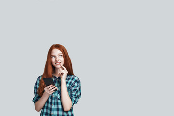 Let me think Young and cute redhead woman in casual wear using her smart phone and smiling while standing against grey background