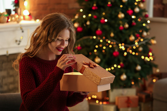 Happy young woman opening Christmas gift at home