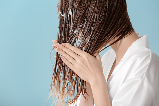 Beautiful young woman applying mousse on her hair after washing against color background
