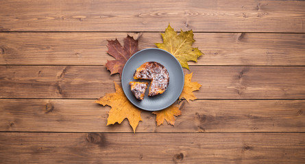Wall Mural - Seasonal autumn background. Frame of maple leaves and a cake over wooden background.