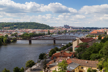 View of the city and bridges over the Vltava River in Prague, Czech Republic, on a sunny day in the summer. Prague (Hradcany) Castle is the background.