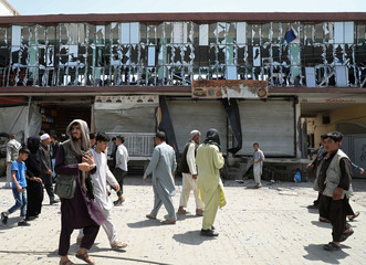 People walk in front of a building with broken windows at the site of a car bomb blast in Kabul