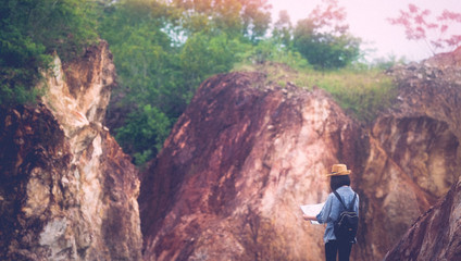 Back of solo travel in local asia, Teenager traveler holding map while hiking on mountain, Solo tourist traveller with map standing on top of stone hill background, Summer travel vacation