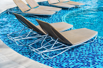 Empty chair for take a seat and relax around outdoor swimming pool in hotel resort for holiday vacation