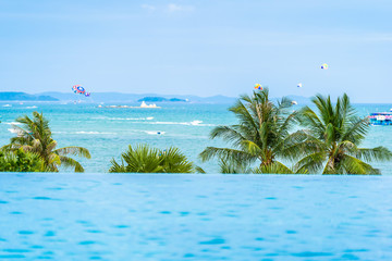 Beautiful outdoor infinity swimming pool with coconut palm tree and sea ocean on blue sky for holiday vacation