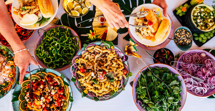 Vertical view of people firends hands taking food from catering table during party celebration - catering and restaurant concept with mixed chef food on a table -coloured background and together
