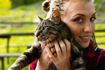Acrylic Prints Loving young woman cuddling her cat to her cheek
