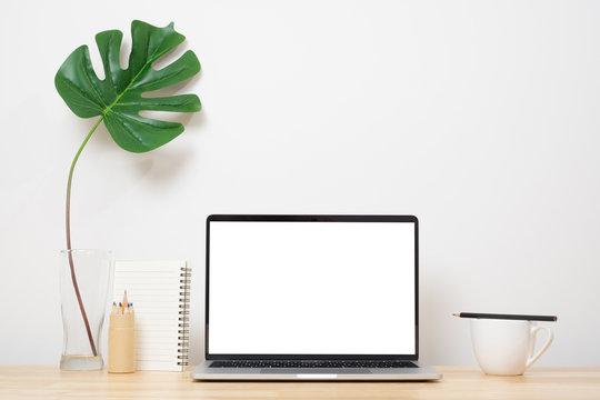Laptop computer blank screen on wood desk. Minimal style desk.