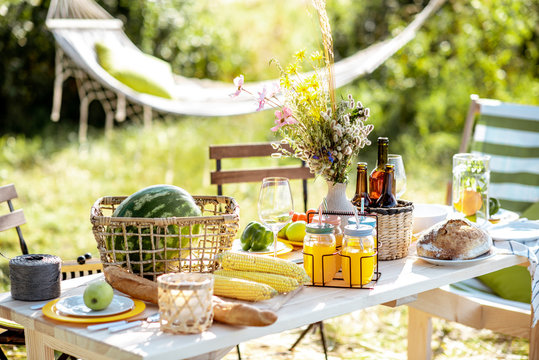 Beautifully decorated lunch table with food, drinks and flowers in the garden