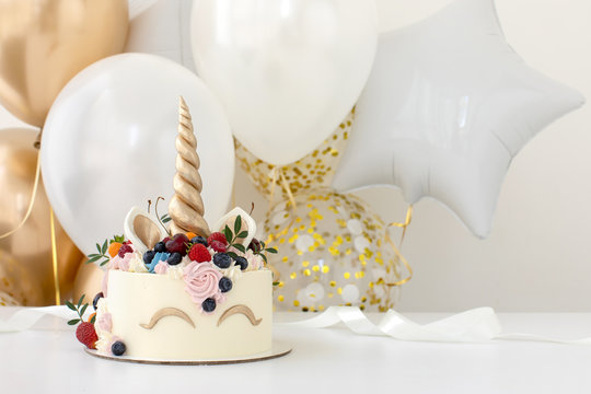 Close up of little girl's birthday party table with unicorn cake
