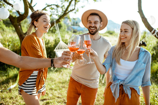 Young and cheerful friends having fun, clinking with wine glasses in the beautifully decorated backyard during a festive meeting or party on a sunny summer evening
