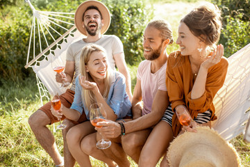 Portrait of a group of cheerful friends sitting together on the hammock, having fun outdoors during a summer days