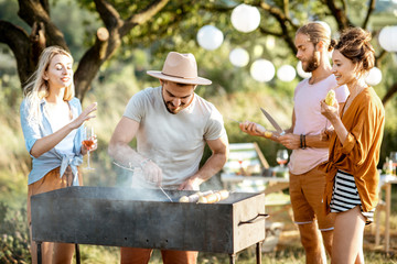 Group of a young friends having barbecue, cooking food in the beautiful garden during a festive lunch on a summer aftenoon