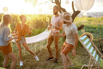 Young and happy friends having fun, dancing together with wine during a picnic in the beautiful garden on a sunset