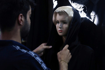 An Iraqi shop owner arranges abaya on a mannequin in the holy city of Kerbala