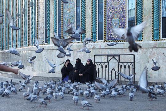 Iraqi women are seen with birds fly near Imam Abbas shrine in the holy city of Kerbala