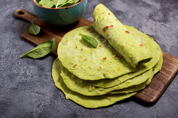 Green tortillas with spinach, round empty tortilla flatbreads for wraps, trendy mexican food, healthy snack concept