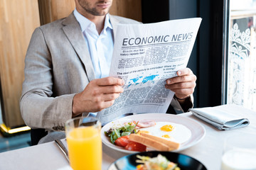 businessman sitting at served table and reading newspaper in cafe