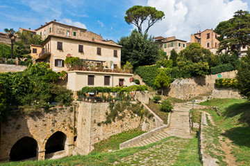 Volterra cityscape inside city walls, vintage houses on a hill surounded by pine and cypress trees, Tuscany, Italy