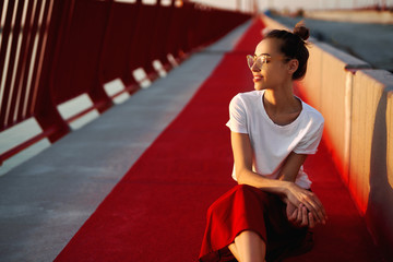 Bright summer lifestyle portrait of young pretty woman in eyewear, red skirt and white T-shirt, sitting on a bright red floor on the bridge.