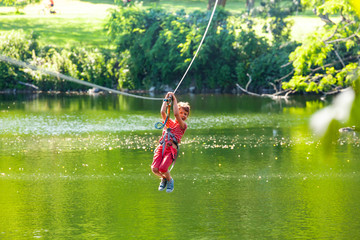 Happy child slide zip line with trolley over lake