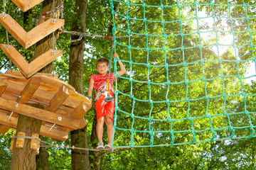 Boy climb from platform to net between trees