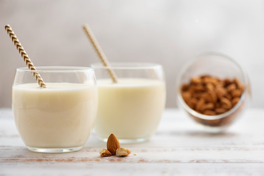 Almond milk in glasses with almond on a light wooden table