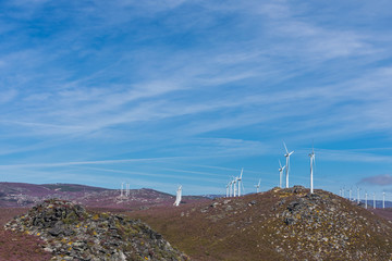 wind turbines over mountains and blue sky