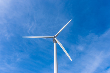 wind turbine over mountains and blue sky
