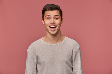 Portrait of cheerful handsome young guy wears in blank long sleeve, looks at the camera with happy expression, stands over pink background.