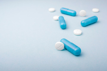 Assorted medicine tablets and capsules on blue background.Copy space for text
