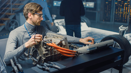 Professional Automotive Engineer in Glasses with a Computer and Inspection Tools is Testing an Used Electric Engine in a High Tech Laboratory with a Concept Car Chassis.
