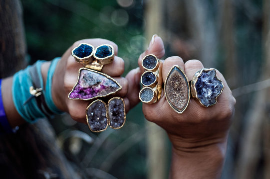 Rings of Power. Semi precious gemstone crystal rings displayed on the beautiful hands of a yoga  woman