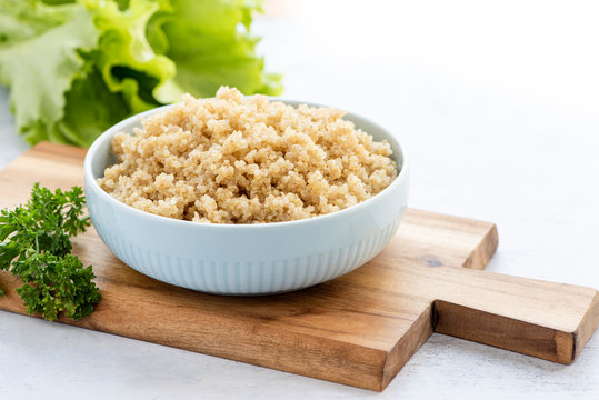 Cooked white quinoa in a ceramic bowl. Healthy vegan food concept.