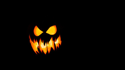 Halloween pumpkin with scary face on black background.