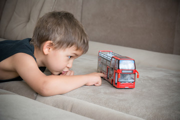 Young boy playing with a toy bus