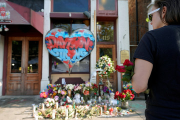 A Oregon District resident stands at a memorial for those killed during Sunday morning's a mass shooting in Dayton
