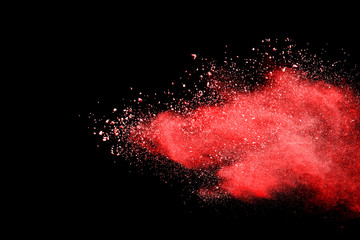 Red powder explosion on black background. Colored cloud. Colorful dust explode. Paint Holi.