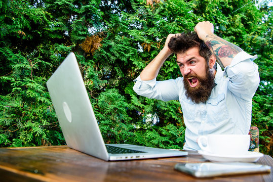Drink coffee and work faster. Deadline is coming. Bearded man freelance worker. Remote job. Freelance professional occupation. Hipster busy with freelance. Wifi and laptop. Slow internet irritating