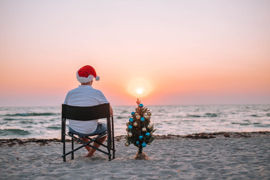 A guy in a santa hat on the beach with a Christmas tree at sunset.