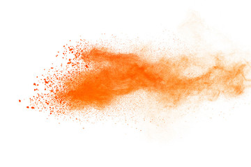 Abstract orange powder explosion. Closeup of orange dust particle splash isolated on white background