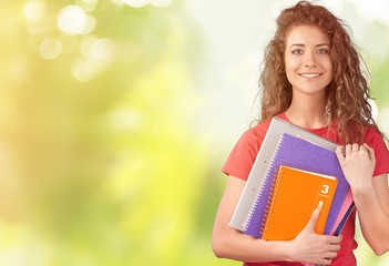 Portrait of a cute young student girl holding colorful notebooks, isolated on background